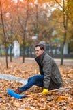 Um indivíduo está sentando-se no freio em um parque do outono Foto de Stock