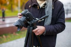 Um indivíduo na roupa morna, em exterior ereto e em fotografar algo em baixo em uma câmera em um tripé fotografia de stock