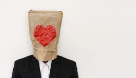 Um indivíduo no terno que veste o saco de papel marrom com forma da charneca fotografia de stock