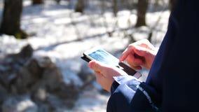 Um indivíduo novo anda abaixo da rua e usa o telefone para o Internet Close-up video estoque