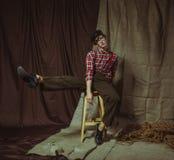 Um indivíduo novo atrativo senta-se em uma cadeira com um pé levantado elevação Imagem de Stock Royalty Free