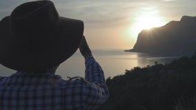 Um indivíduo novo com um chapéu está olhando o por do sol no mar que o sol se ajusta no mar atrás do cabo Admira o curso do verão vídeos de arquivo