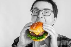 Um indivíduo novo com os vidros que guardam um hamburguer fresco Um estudante muito com fome come o fast food O conceito da gluto imagens de stock royalty free