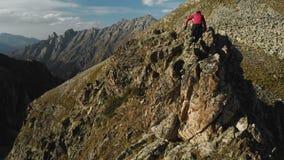 Um indivíduo novo com uma barba, um alpinista em um tampão e os óculos de sol, escalam uma elevação rochosa do cume nas montanhas