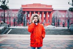 Um indivíduo novo considerável com barba e o revestimento vermelho na capa um estudante usa um telefone celular, escreve, escreve foto de stock
