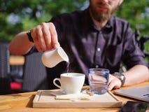Um indivíduo novo derrama um creme no café em um café na tabela Fotos de Stock