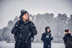 Um indivíduo novo do caminhante com uma trouxa que anda com seus amigos através das madeiras de um inverno fotos de stock