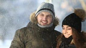 Um indivíduo novo e uma menina vestiram-se na roupa morna do inverno, apreciam a presença de se em um parque nevado do inverno filme