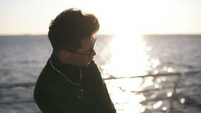 Um indivíduo novo em um blazer preto e em vidros na praia praticou dançar no sol da manhã Dan?as de Expesive fora filme