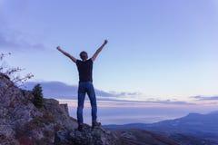 Um indivíduo novo em um t-shirt preto está estando sobre uma montanha, espalhando seus braços para o céu imagens de stock royalty free