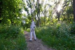 Um indivíduo novo em um terno cinzento dos esportes está oposto ao sol entre fotografia de stock