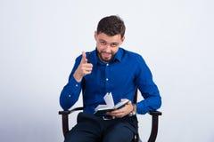 Um indivíduo novo em uma camisa azul senta-se em uma cadeira Fotografia de Stock Royalty Free