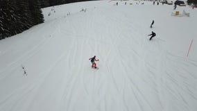 Um indivíduo novo está montando um snowboard abaixo da inclinação alpina filme