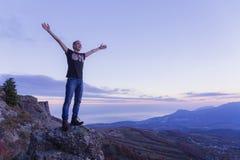 Um indivíduo novo está na borda de um abismo da montanha, espalhando seus braços para o céu contra de um por do sol roxo imagens de stock