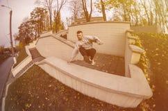 Um indivíduo novo executa um salto através do parapeito concreto fotos de stock