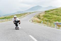 Um indivíduo novo no capacete está montando em uma estrada secundária na alta velocidade na chuva fotos de stock royalty free