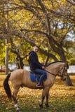 Um indivíduo novo sério, vestido na roupa exterior morna, senta-se montado em um cavalo No parque do outono imagens de stock royalty free