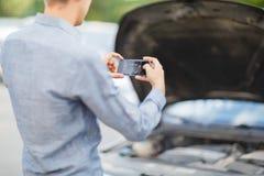 Um indivíduo novo toma uma imagem de um motor de automóveis fotografia de stock
