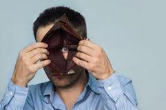 Um indivíduo olha através de um furo no fundo de uma carteira de couro vazia mostrando emoções e a frustração negativas, decepção fotos de stock