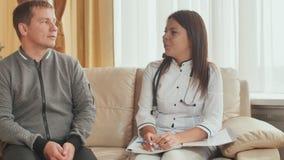 Um indivíduo paciente e um doutor da moça dão o conselho em um hospital video estoque