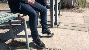 Um indivíduo senta-se em um banco em uma parada do ônibus e agita-se seus pés na antecipação video estoque