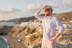 Um indivíduo viril romântico com uma barba, uns óculos de sol vestindo e um chapéu está lateralmente em uma costa rochosa e olha  imagens de stock