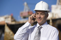 Um inspector da plataforma petrolífera no telefone imagens de stock