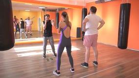 Um instrutor masculino caucasiano ensina um homem e uma menina farpados o perfurador direito na arte marcial, autodefesa, gym, mo video estoque