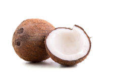 Um inteiro e um corte frescos em meios cocos, em um fundo branco Nuts marrom brilhante rachado e inteiro completamente dos nutrie foto de stock royalty free