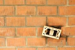 Um interruptor de ligar/desligar quebrado na parede de tijolo alaranjada Fotos de Stock