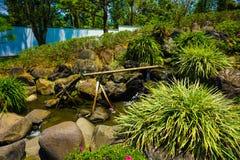 Um japonês ou um japão graden o estilo com linha de bambu da tubulação da água com grama verde e água que fluem na lagoa pequena  fotografia de stock royalty free