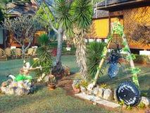Um jardim agradável com palmas e flores Foto de Stock