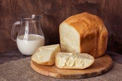Um jarro de leite e de pão fresco em uma tabela de madeira Imagem de Stock