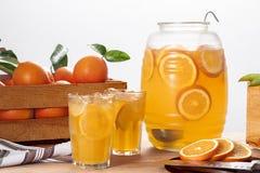 Um jarro e vidros da limonada alaranjada Foto de Stock Royalty Free