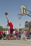 Um jogador de basquetebol novo executa um lance ao afundanço cont Imagens de Stock