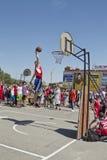 Um jogador de basquetebol novo executa um lance ao afundanço cont Imagem de Stock