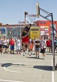 Um jogador de basquetebol novo executa um lance ao afundanço cont Imagem de Stock Royalty Free