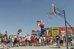Um jogador de basquetebol novo executa um lance ao afundanço cont Fotografia de Stock