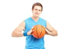Um jogador de basquetebol novo que guardara um basquetebol e que olha o Ca Fotografia de Stock Royalty Free