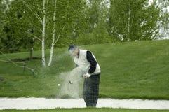 Um jogador de golfe bate para fora uma esfera imagens de stock
