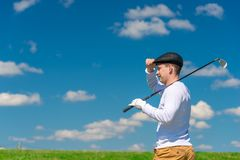 Um jogador de golfe que veste um tampão com um clube de golfe em seu ombro olha o aw fotografia de stock royalty free