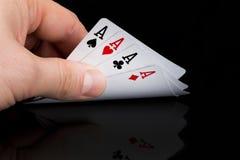 Um jogador de p?quer olha seus cart?es aumentando os em uma tabela preta imagem de stock royalty free
