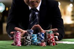 Um jogador de pôquer usou as mãos que empurram em todas suas microplaquetas para a aposta Foto de Stock Royalty Free