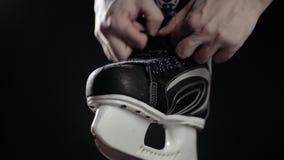 Um jogador no hóquei, laços ata em patins, um fundo preto O fim acima do homem da mão prepara-se para o canadense do gelo do jogo video estoque