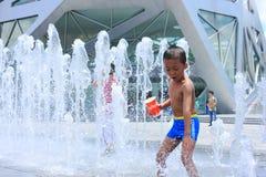 Um jogo asiático do menino pela fonte de água Imagens de Stock Royalty Free