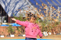 Um jogo da menina do Malay com as folhas secas do outono Foto de Stock