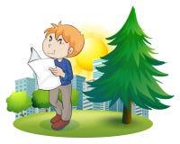 Um jornal da leitura do homem perto do pinheiro Imagens de Stock