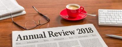 Um jornal em uma mesa de madeira - revisão anual 2018 fotografia de stock