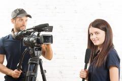 Um journalista e um operador cinematográfico da jovem mulher Imagem de Stock Royalty Free