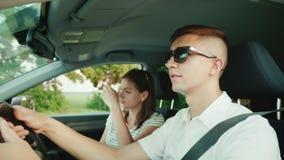 Um jovem acopla discussões no carro, tem uma conversação desagradável Problemas de uma família nova video estoque